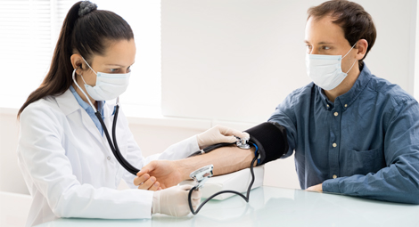 Female doctor wearing a mask checking the blood pressure of a male patient also wearing a mask